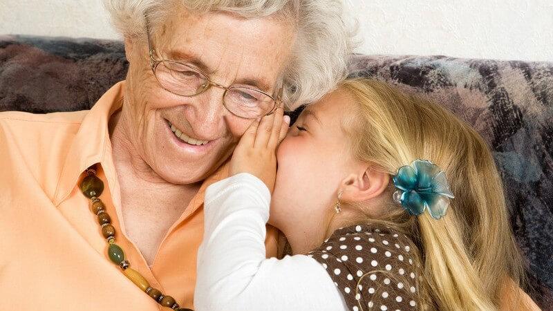 Enkelin sitzt mit Oma auf der Couch und flüstert ihr etwas ins Ohr