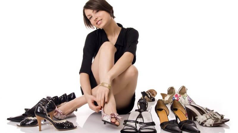 Junge, dunkelhaarige Frau sitzt auf dem Boden, umgeben von mehreren Paar Schuhen