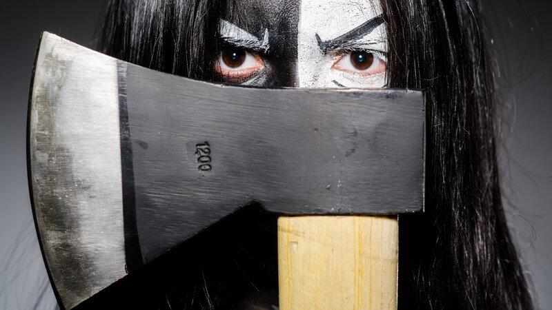 Halloween - Schwarz-weiß geschminkte Frau hält Axt vor ihr Gesicht