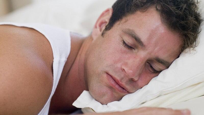 Junger Mann liegt auf Bauch im Bett und schläft