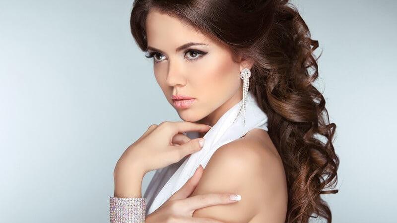Portrait einer hübschen Frau in weißem Neckholderkleid, mit braunen Locken und funkelndem Ohr- und Armschmuck