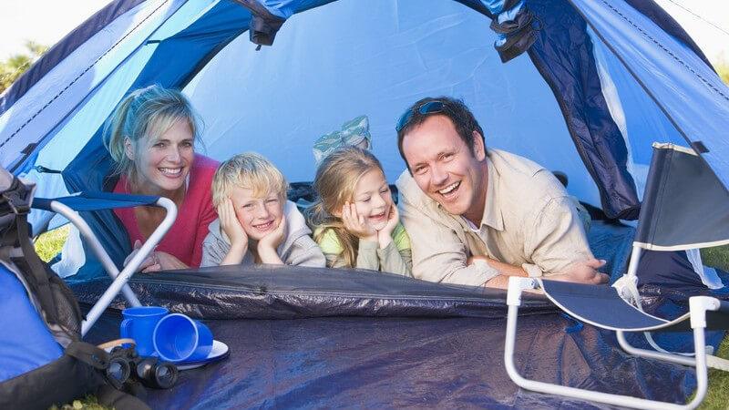 Junge Eltern liegen mit zwei kleinen Kindern im Zelt und lachen in Kamera