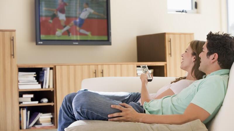 Seitenansicht junges Paar sitzt auf Couch und schaut Fußball im Fernsehen