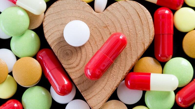 Bunte Pillen und Kapseln umringen ein Herz aus Holz