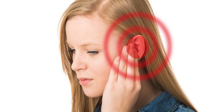 Junge Frau hält sich das Ohr, rot markiert, Tinnitus