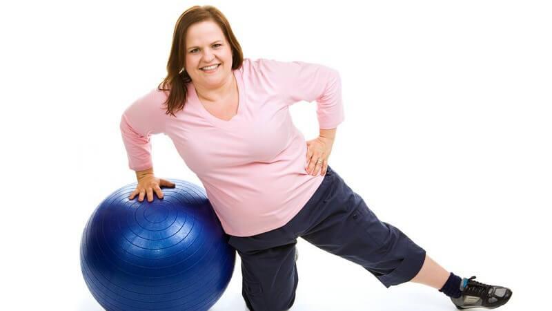 Übergewichtige Frau macht Übungen am Gymnastikball
