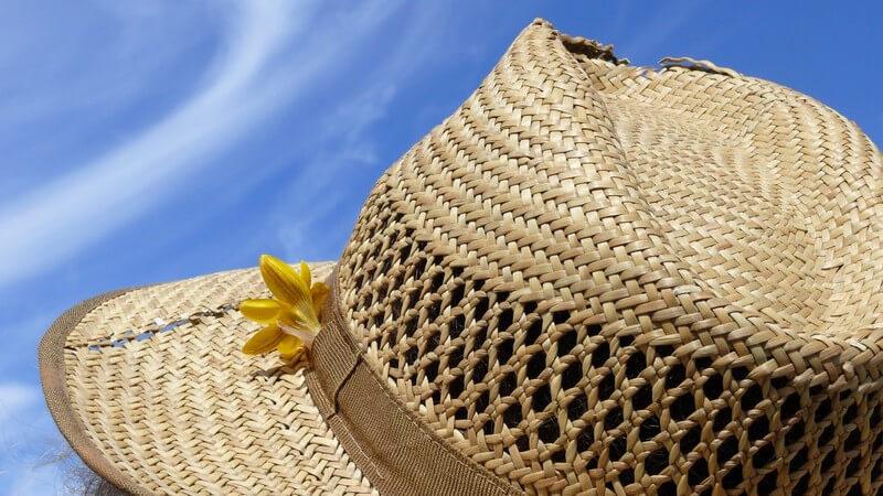 Nahaufnahme Strohhut mit gelber Blume, blauer Himmel im Hintergrund