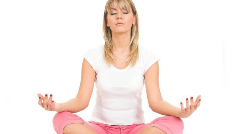 Blonde, junge Frau in rosa Sporthose und weißem Sport-Tshirt sitzt im Schneidersitz mit geschlossenen Augen und meditier