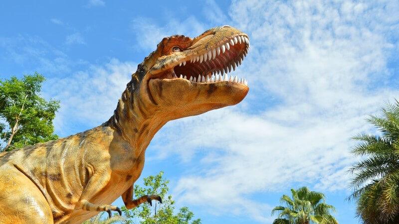 Dinosaurier-Modell unter blauem Himmel und Palmen