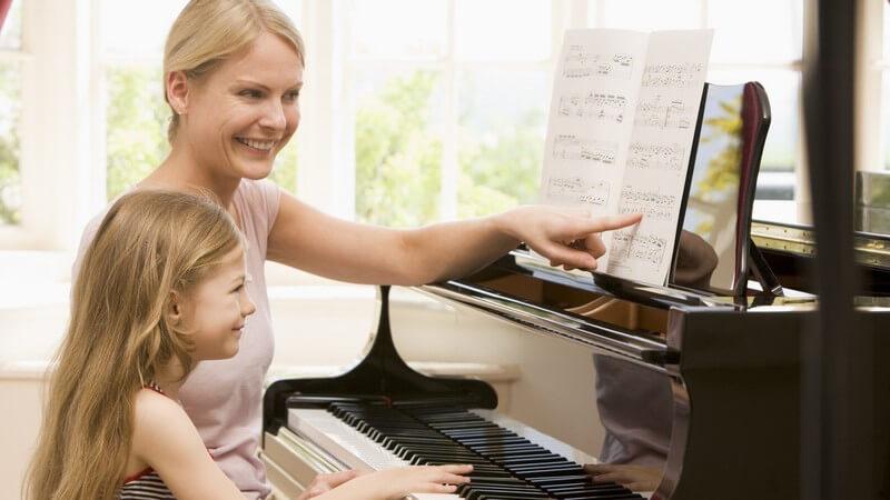 Kleines Mädchen sitzt am Klavier und spielt nach Noten, daneben sitzt Mutter, beide lächeln