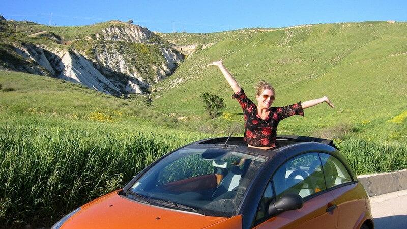 Frau steht im Auto und schaut aus Schiebedach hervor, im Hintergrund Berglandschaft