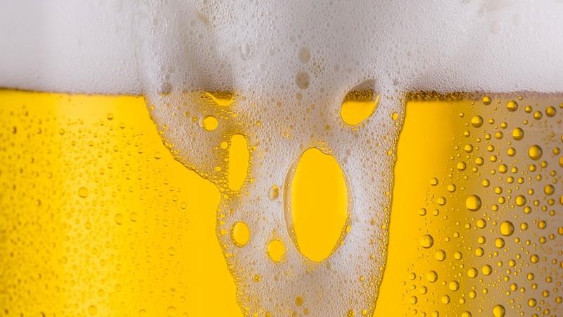 Nahaufnahme eines hellen Biers mit Schaumkrone, Schaum läuft leicht über