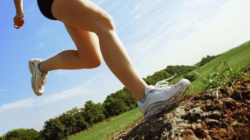 Frauenkörper im Sportoutfit beim Joggen unter blauem Himmel