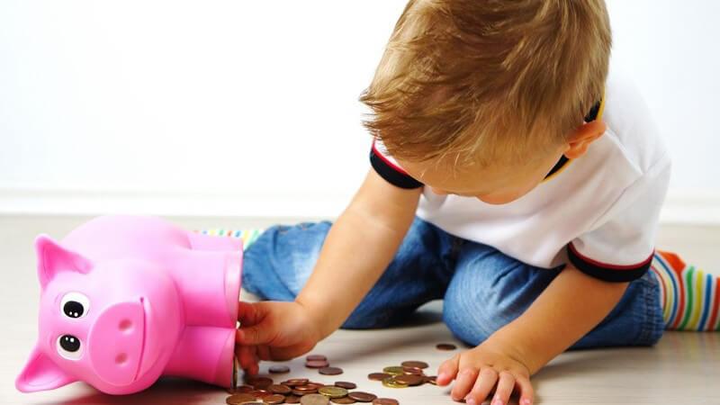 Kleiner Junge sitzt auf dem Boden und leert ein pinkes Sparschwein