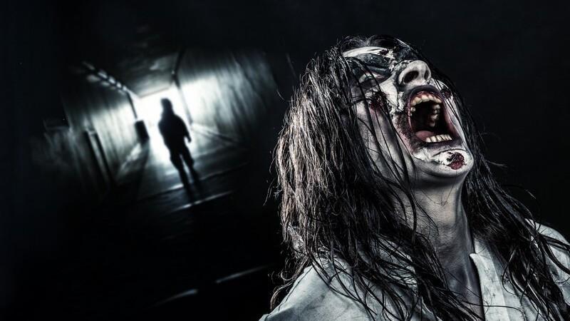 Schreiende Zombie-Frau mit langen schwarzen Haaren am Ende eines dunklen Tunnels