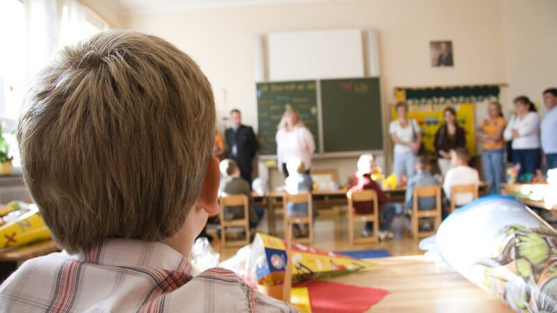 Erster Schultag, Schüler sitzen im Klassenraum, Eltern stehen am Rand