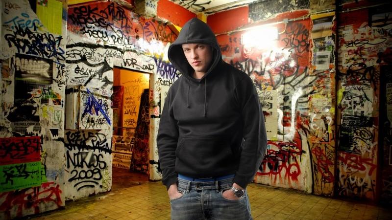 Jugendlicher in Kapuzenpulli vor Graffitiwänden