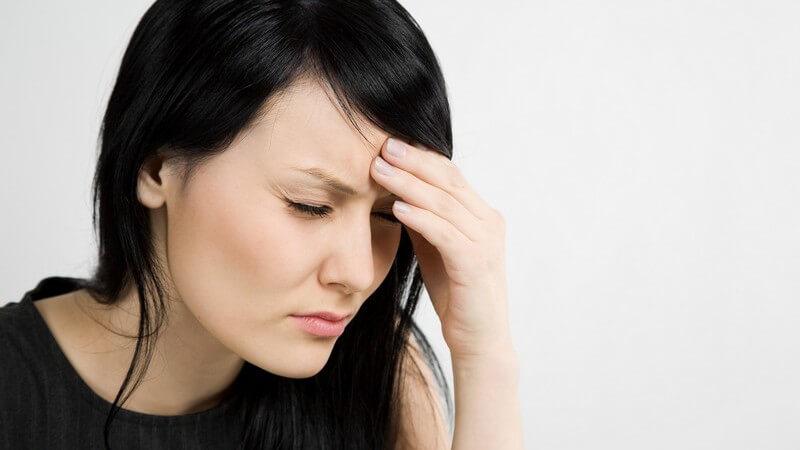 Dunkelhaarige Frau fasst sich an die Stirn, hat Kopfschmerzen