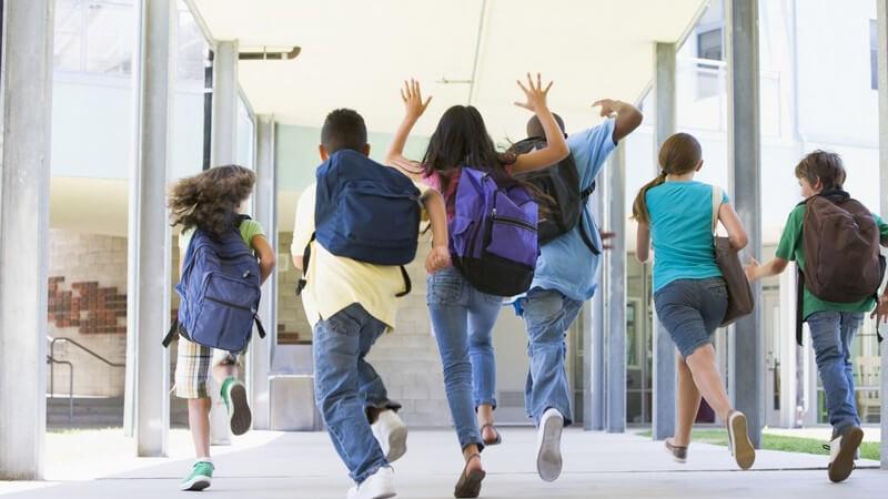 Rückenansicht sechs Schüler einer Grundschule laufen zum Ausgang