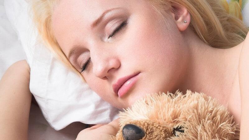 Junge Frau schläft mit Teddybären im Arm