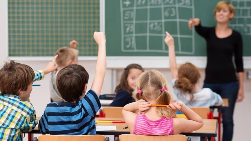 Lehrerin mit Grundschülern im Unterricht, einige zeigen auf