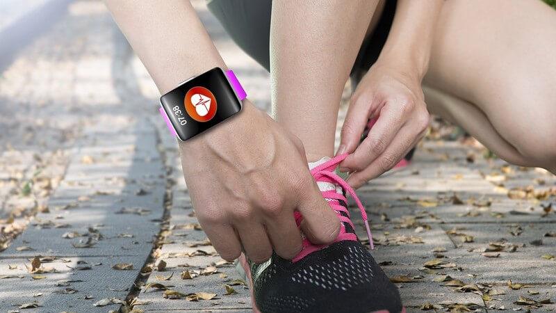 Läuferin mit Fitnessuhr am Handgelenk schnürt sich auf dem Asphalt ihre pinken Laufschuhe