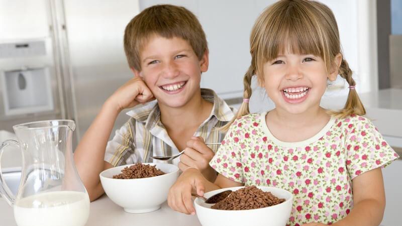 Zwei kleine Kinder am Frühstückstisch mit Müsli, beide lachen