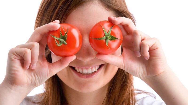 Junge Frau, lächelnd, hält zwei frische Tomaten vor ihre Augen
