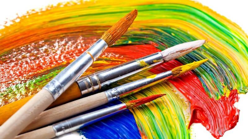 Pinsel voll mit Farbe liegen auf Malerei