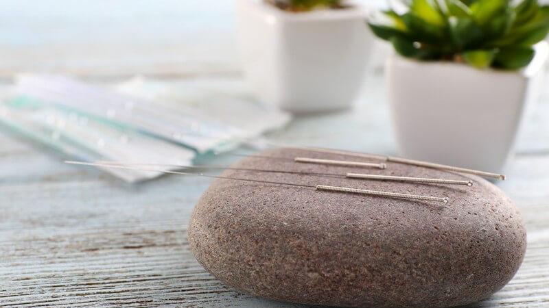 Akupunkturnadeln liegen auf einem Stein auf einem Holztisch