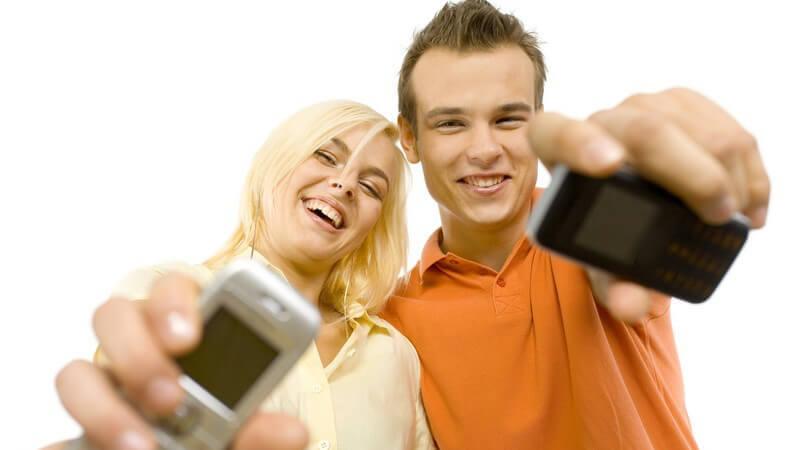 Junges lachendes Paar streckt Handy in Kamera