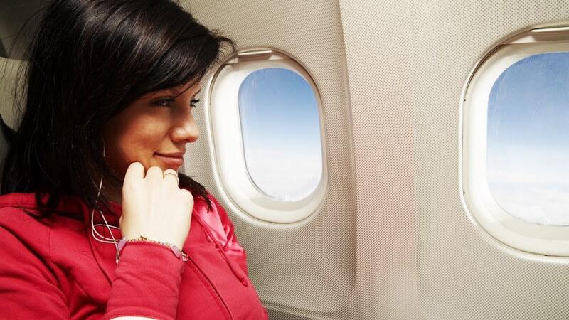 Junge Frau sitzt lächelnd im Flugzeug am Fensterplatz