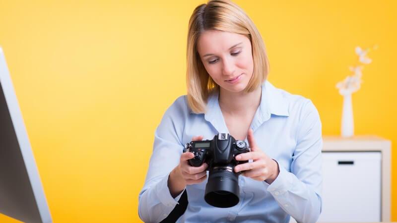 Fotografin sitzt vor einem Computer und schaut auf das Display ihrer Digitalkamera, gelber Hintergrund