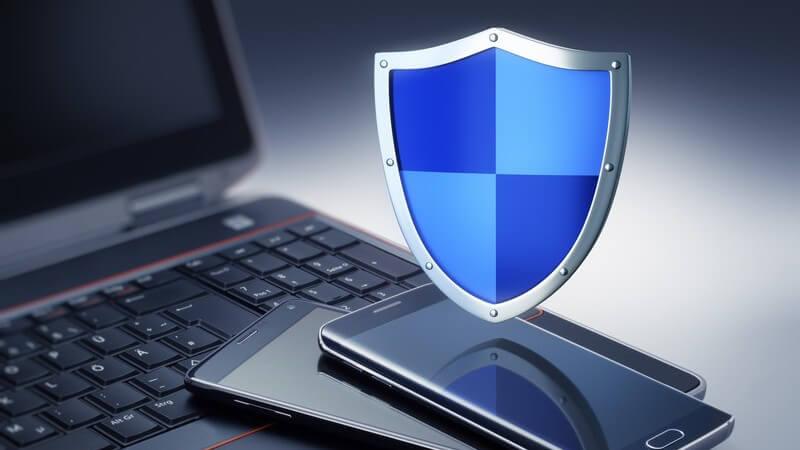 Blaues Wappenschild schwebt über einem schwarzen Laptop und zwei Smartphones