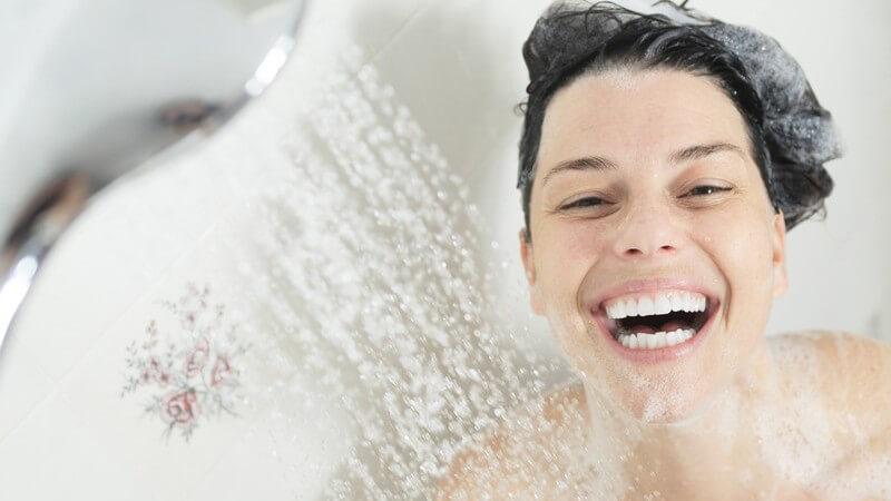 Frau mit Schaum im Haar steht lachend unter der Dusche