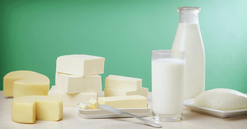 Milch in Glasflasche und Glas, daneben Milchprodukte wie Butter und Käse