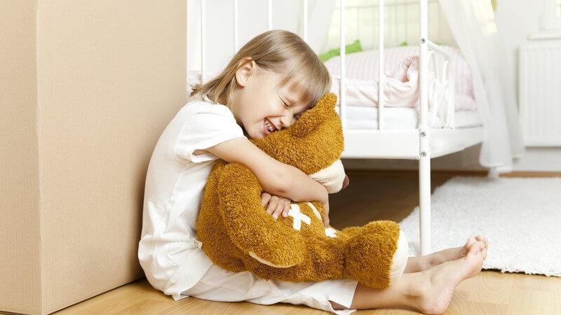 Kleines Mädchen sitzt vor ihrem Bett und hält Teddy fest im Arm