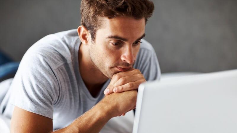 Mann liegt auf Bett und schaut auf Notebook-Bildschirm