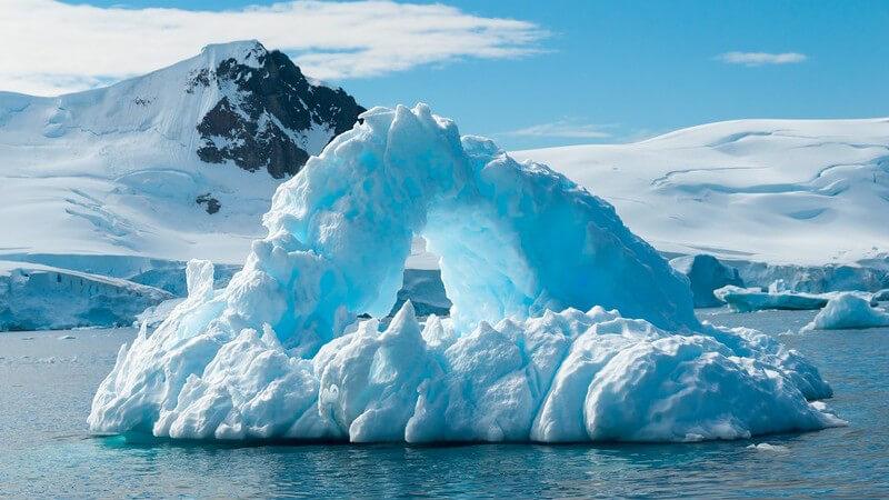 Antarktis: Eisberge im Wasser unter blauem Himmel