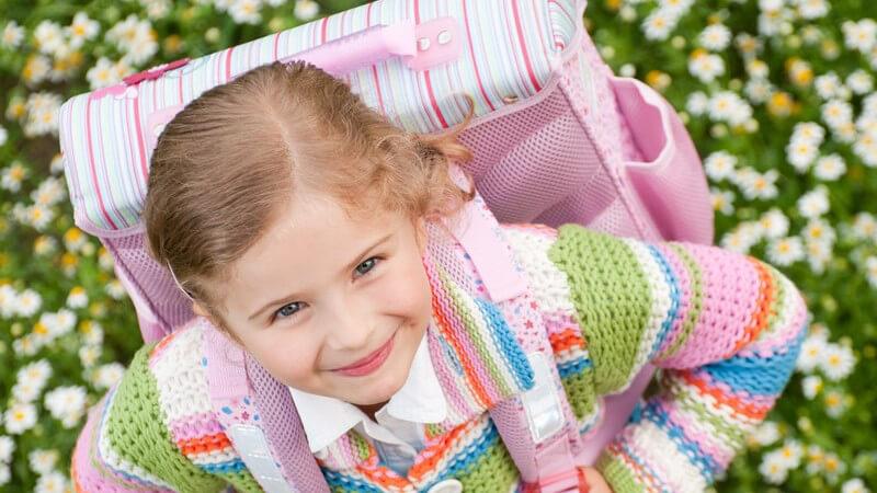 Kleines Mädchen mit Schulrucksack steht in Blumenwiese und schaut nach oben in Kamera