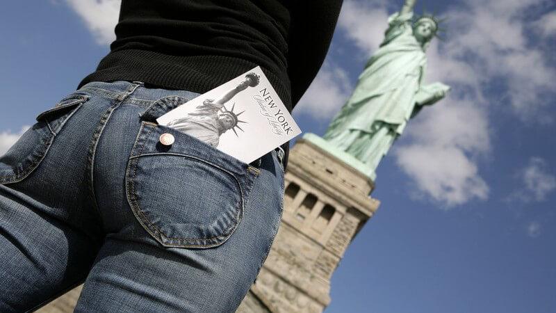 New York, Rückansicht Frauenkörper vor Freiheitstatue, in Hosentasche Postkarte