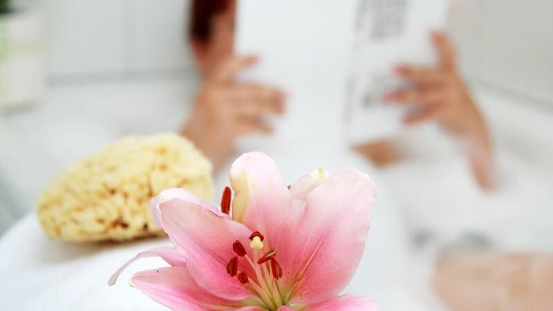 Frau in Badewanne nimmt Schaumbad und liest ein Buch