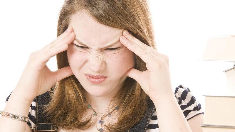 Schülerin greift sich an den Kopf und runzelt die Stirn, Stress beim Lernen