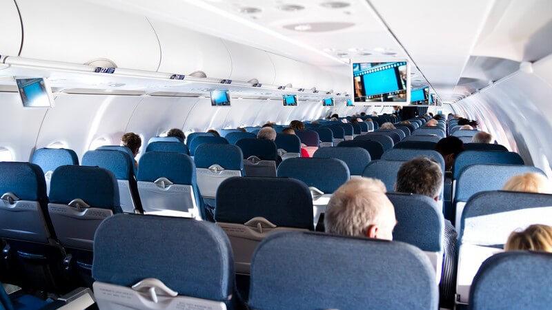 Blick aus einer hinteren Reihe durch ein Flugzeug mit blauen Sitzen