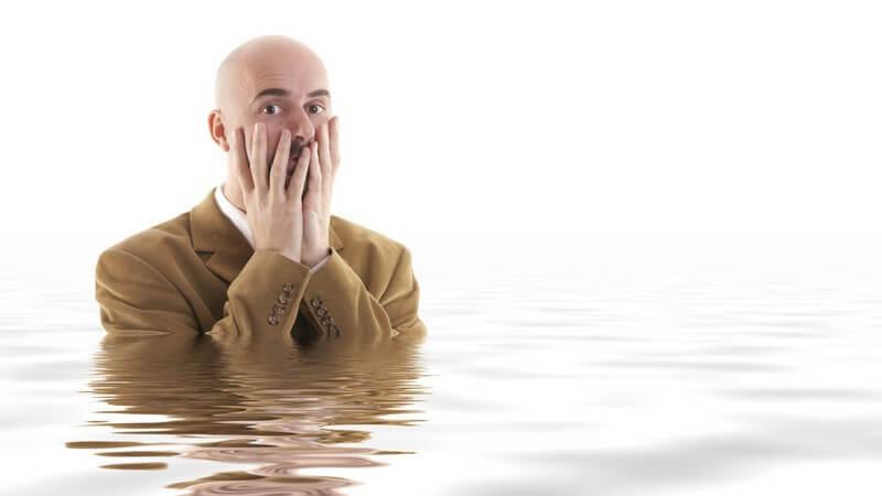 Mann im Anzug steht fast bis Schultern im Wasser, Hände erschrocken vor dem Gesicht