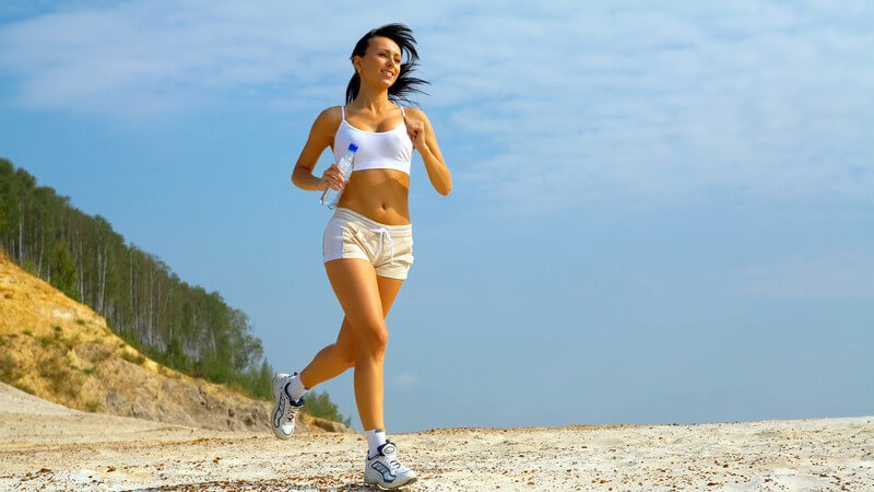 Brünette Frau in kurzer Sportbekleidung mit Wasserflasche beim Laufen