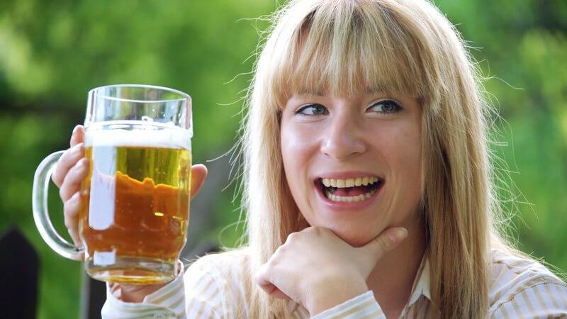 Junge lachende Frau hält Krug mit Bier nach oben
