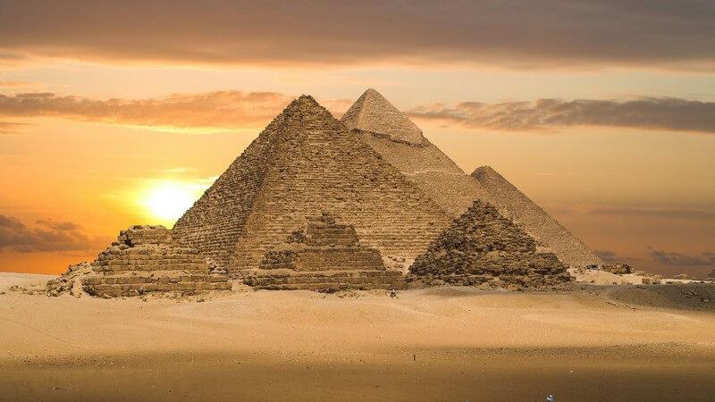 Drei Reiter in Wüste, im Hintergrund Pyramiden im Sonnenuntergang