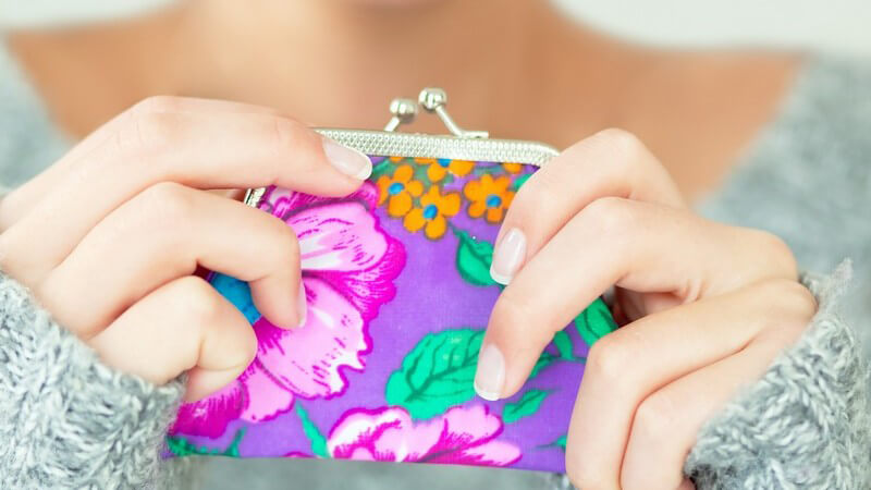 Frau in Stickpullover hält Geldbörse im Händen