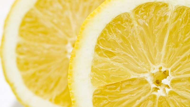 Zwei frische Zitronenscheiben auf weißem Hintergrund